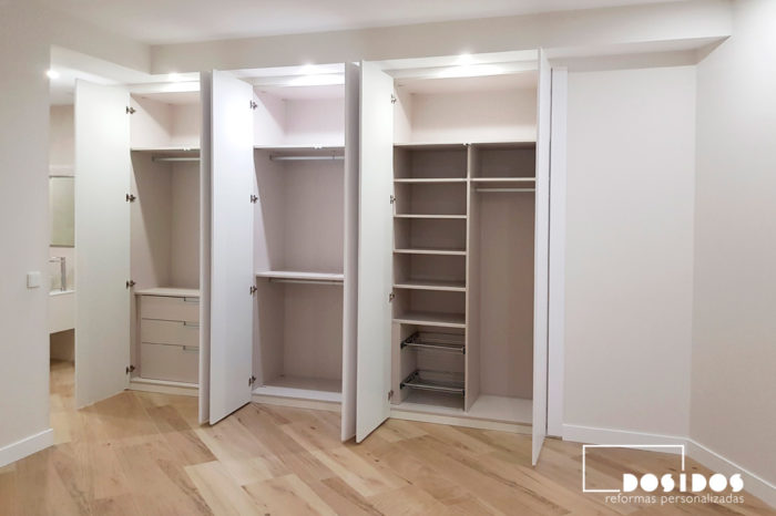 Gran armario en habitación de matrimonio con mucho espacio de almacenaje, vista puertas abiertas.