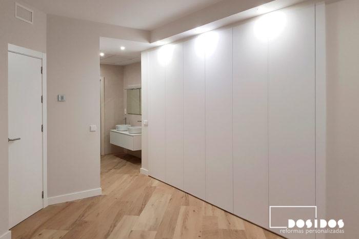 Habitación de matrimonio en suite con un enorme armario y baño abierto.