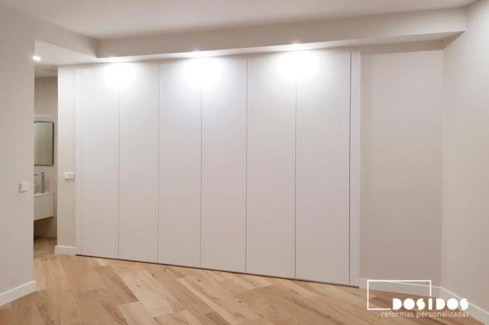 Gran armario en habitación de matrimonio con mucho espacio de almacenaje, vista puertas cerradas.