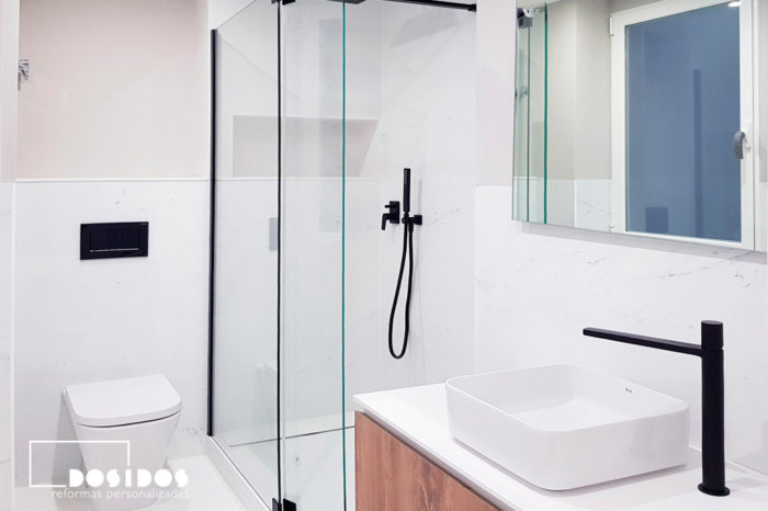 Reforma del baño marmolizado blanco, grifería negra y detalles decorativos en negro.