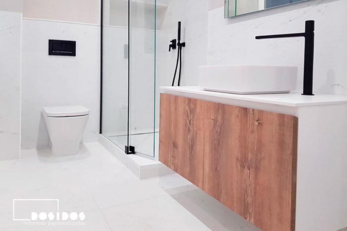Baño marmolizado blanco, grifería negra y mueble de baño en madera con lavabo sobre encimera.