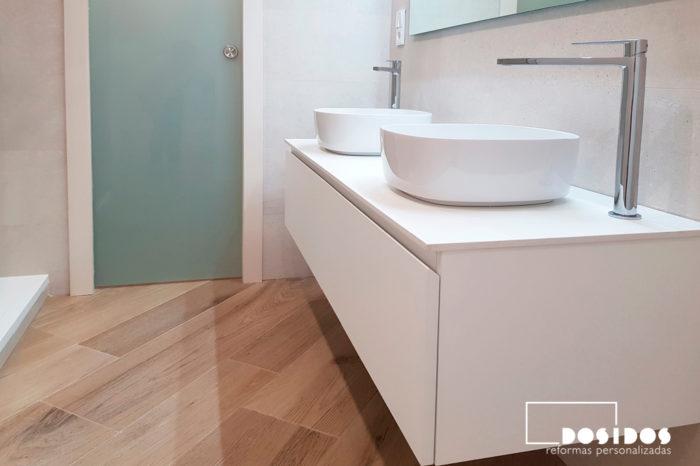 Baño con mueble suspendido doble con lavabos sobre encimera blancos y puerta corredera de cristal.