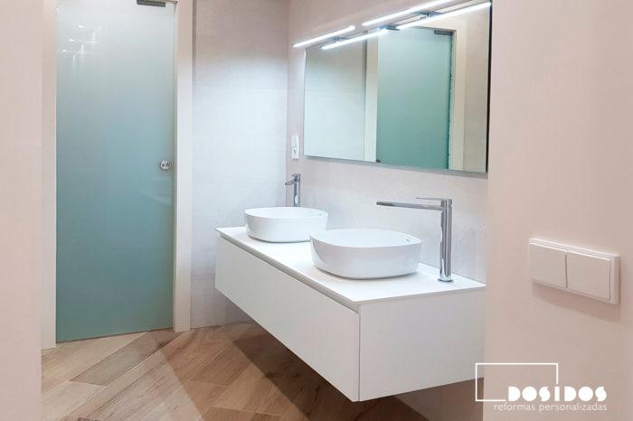 Baño azulejos caliza beige con mueble suspendido de 2 senos blanco, puerta corredera de cristal.