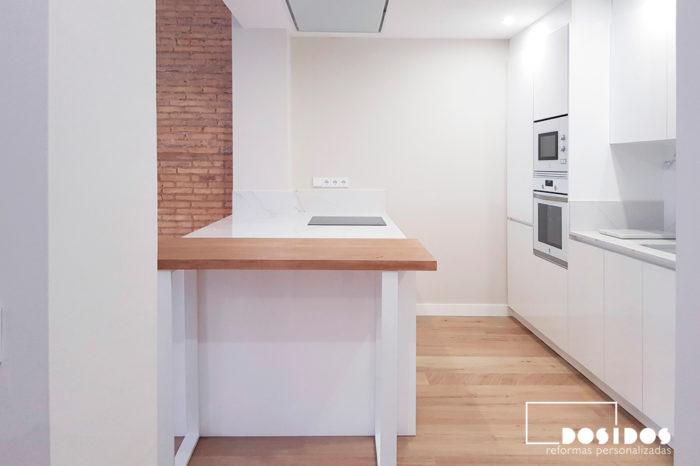 Cocina blanca con una isla y barra de madera para desayuno, abierta al salón con una pared de ladrillo macizo.
