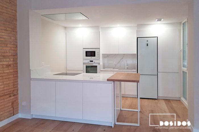Reforma espectacular de cocina blanca con isla, abierta al salón.