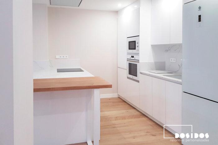 Cocina blanca abierta al salón con isla y barra auxiliar de madera.
