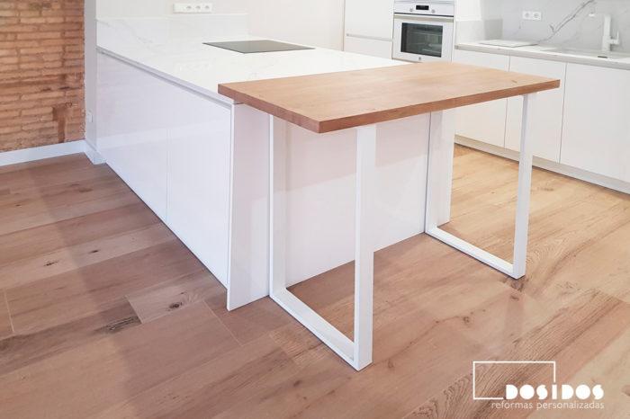 Cocina blanca con isla y barra de madera maciza con patas de hierro en color blanco para desayunos.
