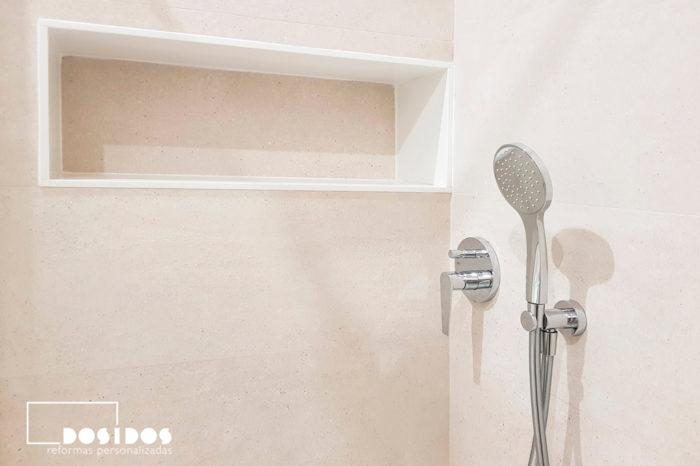 Detalle de la ducha de un baño con azulejos caliza beige, estante hornacina y grifería empotrada cromada.