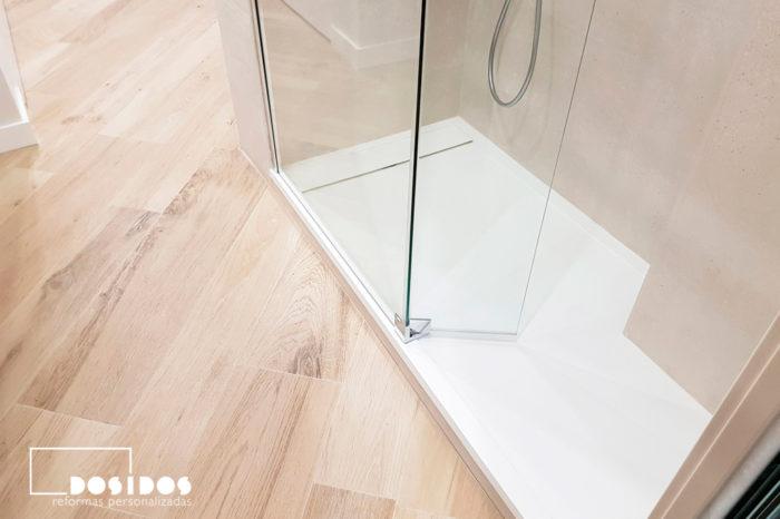 Baño con el suelo imitando a madera, plato de ducha blanco playa y mampara transparente fijo más abatible.