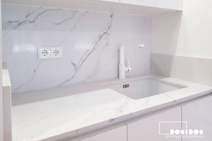 Encimera y frente de cocina en compac calacatta con el fregadero de fibra bajo encimera y el grifo en color blanco.