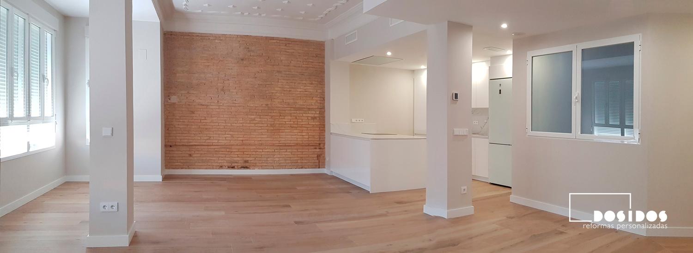 Gran reforma de un salón diáfano con pared de ladrillo macizo y cocina abierta con isla.