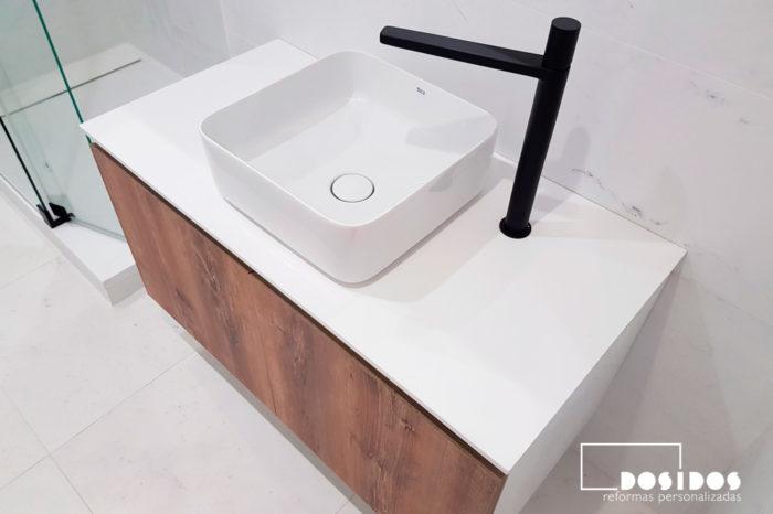 Baño con mueble de madera con lavabo sobre encimera, grifo especial negro y azulejos mármol blanco.