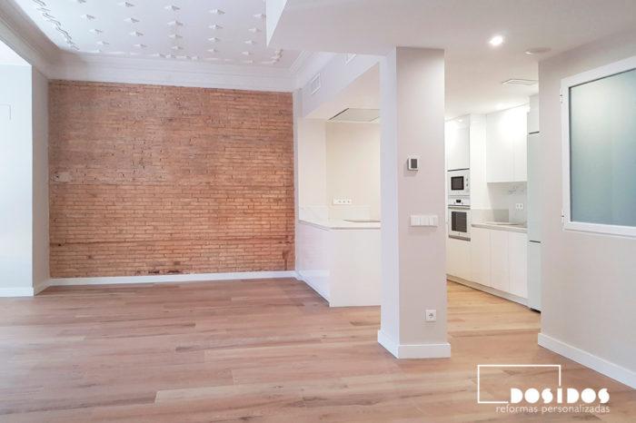 Salón diáfano con el suelo de azulejo imitación a parquet marca Porcelanosa y con una pared de ladrillo macizo y la cocina abierta.