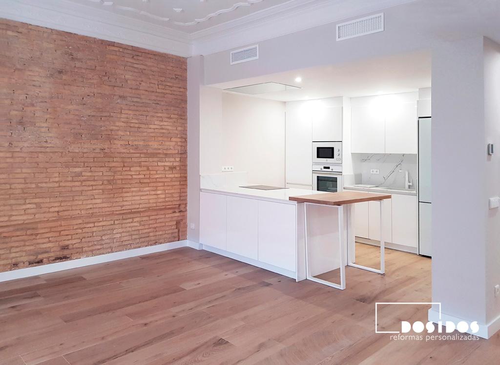 Salón con una pared de ladrillo, cocina blanca abierta al salón.
