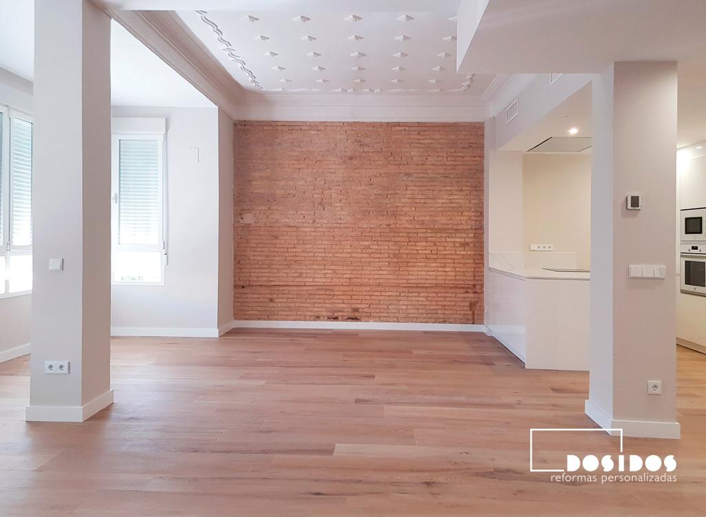 Reforma integral de un gran salón diáfano y con una pared de ladrillo visto.