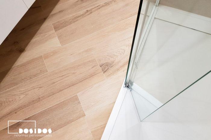 Vista del suelo de un baño imitación a madera y la ducha plana blanca con mampara transparente fijo más abatible.