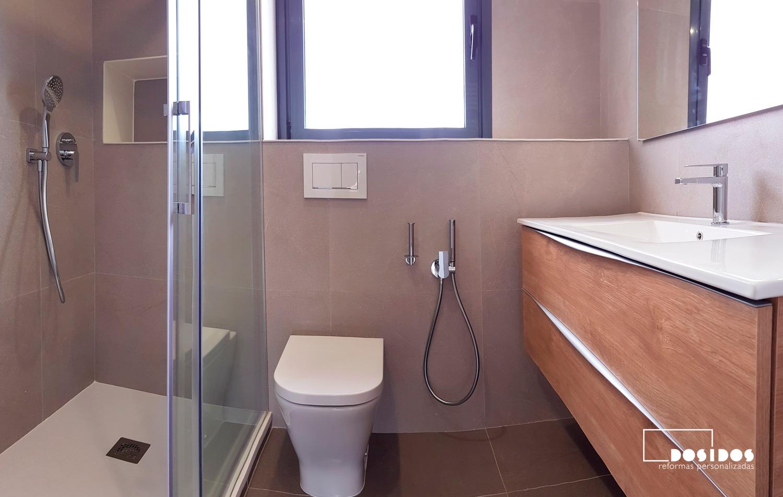 Baño completo con plato de ducha extraplano, inodoro empotrado, grifo de bidé wc y mueble grande de madera.