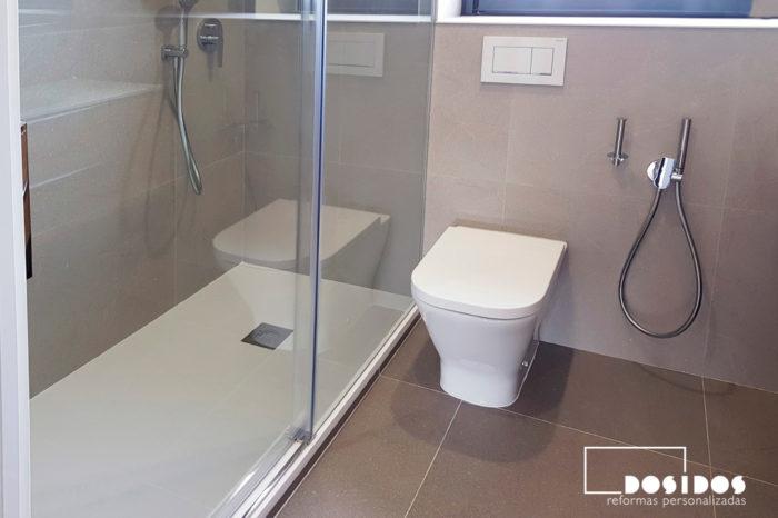 Baño con plato de ducha blanco extraplano, inodoro empotrado y grifo de bidé wc.