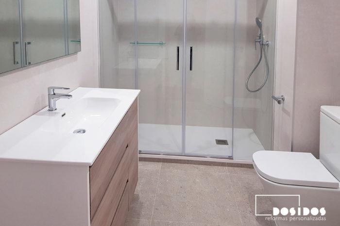 Baño espacioso y luminosa con mueble madera clara, ducha extraplana grande, mampara corredera transparente e inodoro.