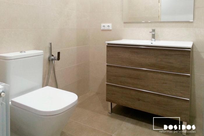 Baño pequeño moderno con mueble de madera vintage tres cajones, lavabo de cerámica e inodoro con grifo de bidé wc.