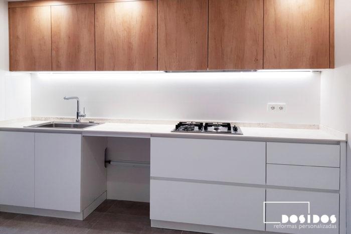 Cocina lineal blanca con detalles en madera y encimera dekton nilium