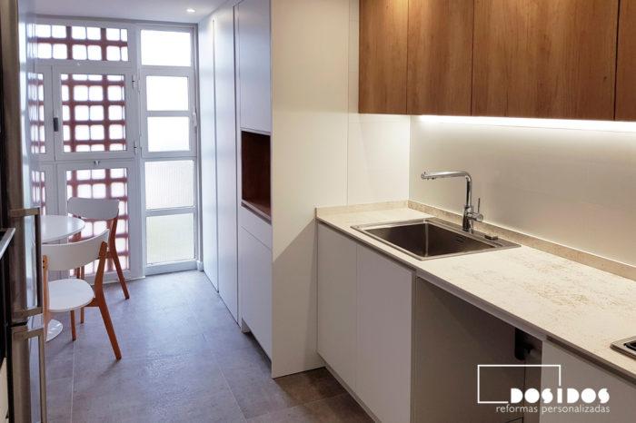 Reforma de cocina con muebles blancos y madera, hueco decorativo en columna almacenaje, espacio para office y desayunos.