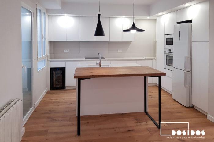 Cocina grande con isla y barra de madera con patas negras, muebles y encimera blancos. Suelo de madera natural