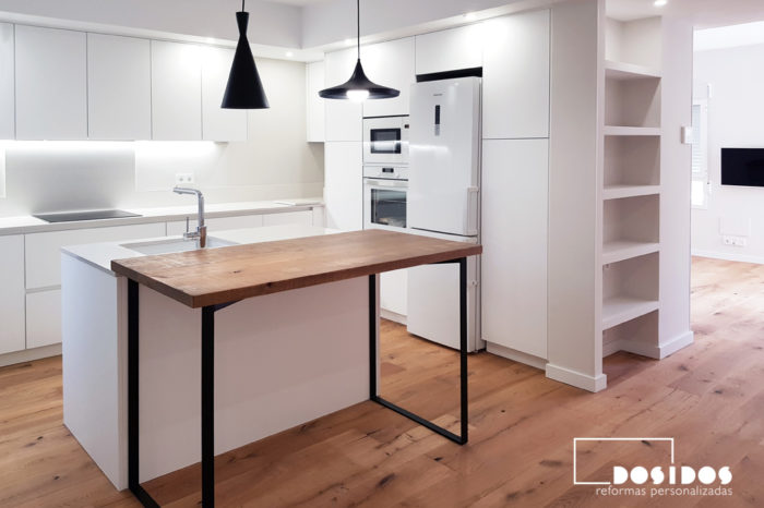 Cocina abierta con isla y barra de madera con patas negras, muebles y encimera blancos. Estantería de pladur en pasillo hacia el salón