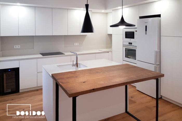 Cocina con isla y barra de madera con patas negras, muebles y encimera blancos.