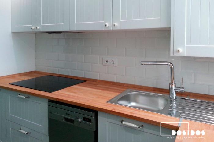 Cocina vintage con muebles blancos y encimera de madera con frente en azulejos brick blancos.