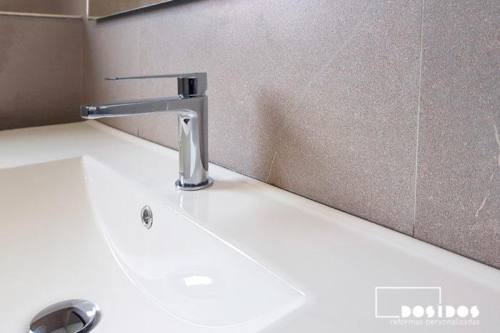 Detalle del lavabo de porcelana en mueble y grifo cromado, azulejos de baño imitación piedra gris.
