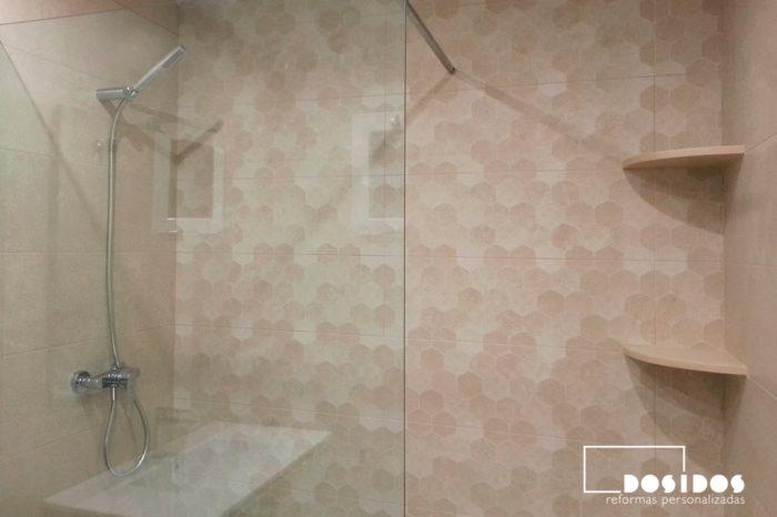 Detalle de la ducha con azulejos marrones con dibujos hexagonales y dos estantes en la esquina.
