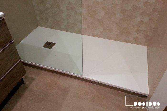 Detalle del plato de ducha extraplano con azulejos marrones con dibujos hexagonales y mampara fijo transparente.