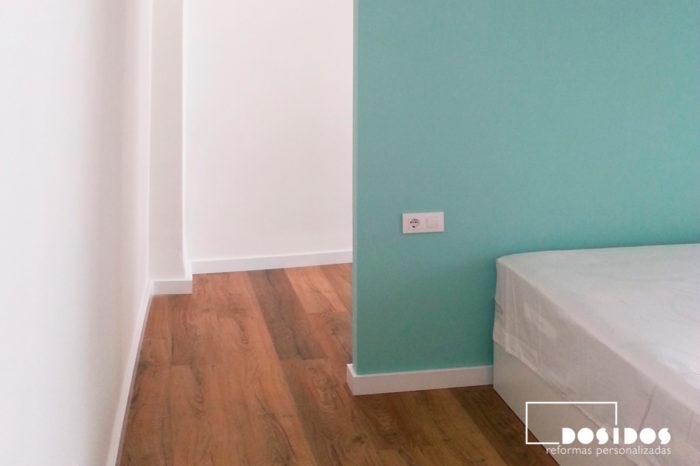 Entrada al vestidor con la pared del cabezal en color verde y suelo con parquet.