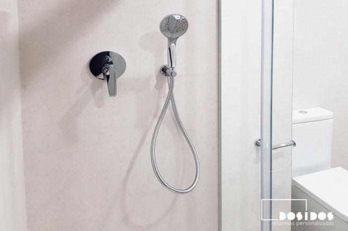 Ducha de baño luminoso, con azulejos claros y grifos de ducha empotrados.