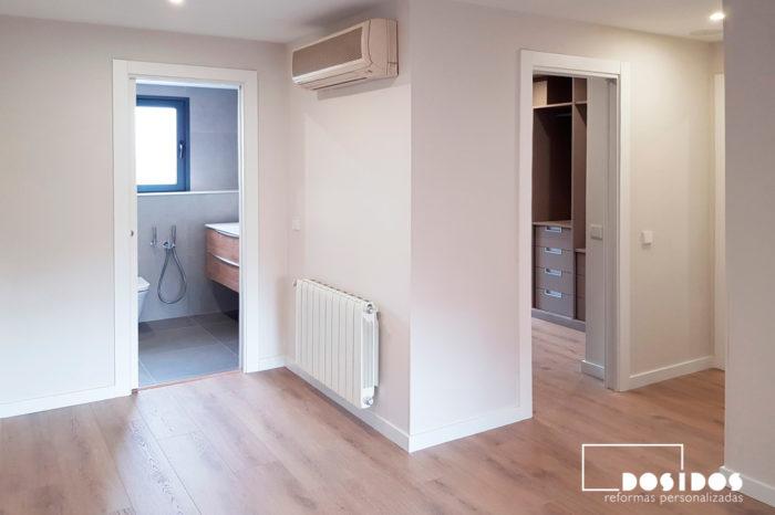 Reforma de la habitación de matrimonio en suite con baño y vestidor abierto, con puertas de acceso correderas blancas..