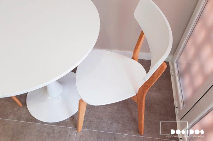 Mesa redonda y sillas de diseño para office de cocina blanca.