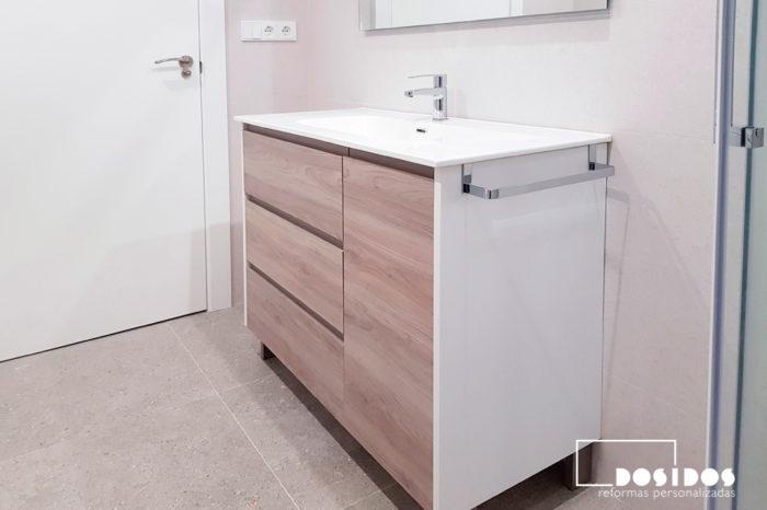 Un baño muy luminoso, con azulejos claros, mueble con gran almacenamiento, en madera clara y blanco con tres cajones y una puerta.