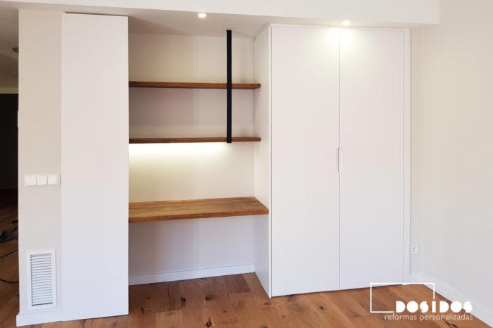 Oficina en casa en el salón con un escritorio de madera, estanterías y un armario
