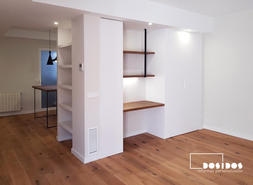 Espacio en el salón oficina en casa, con una escritorio de madera, estantería y un armario