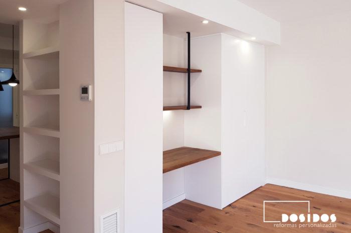 Espacio en el salón oficina en casa junto a la cocina, con una escritorio de madera, estantería y un armario