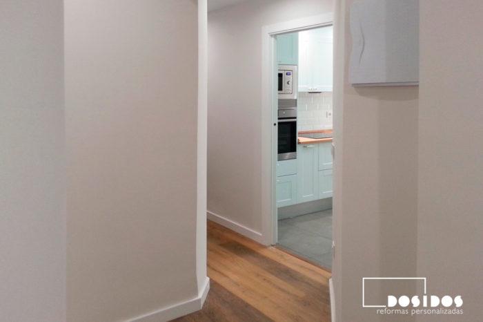 Pasillo con suelo de parquet y vista de la entrada a una cocina vintage con puerta corredera.