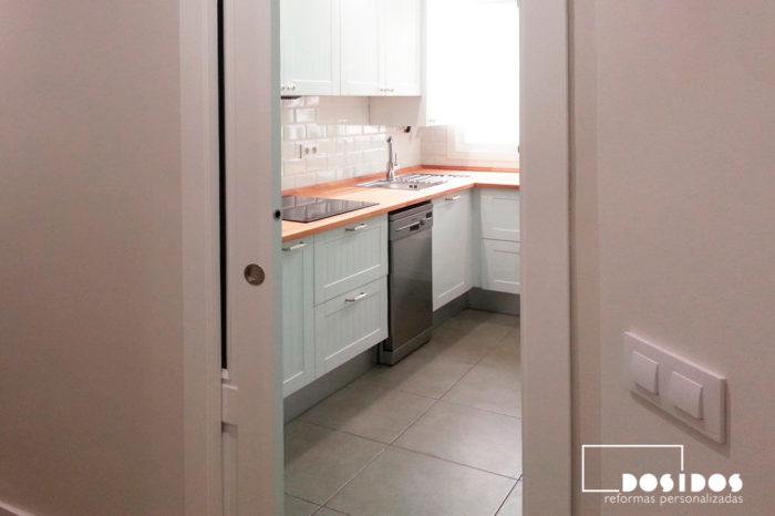 Detalle de la entrada con puerta corredera embutida a una cocina vintage.