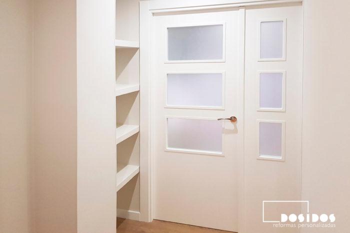 Recibidor con estantería de escayola decorativa para disimular un pilar y puerta doble entrada al salón vidriera blanca.