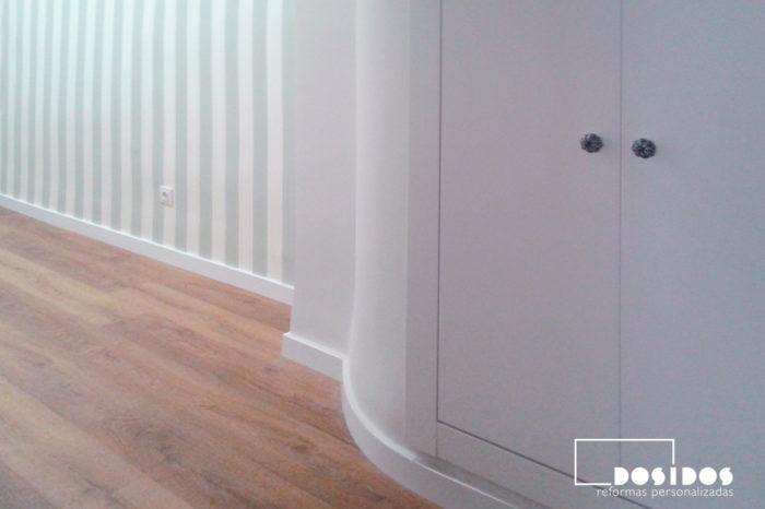 Recibidor con armario en pared curva y decoración de parad con papel pintado a rayas verdes.