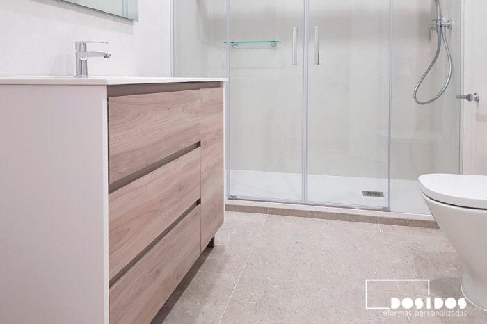 Reforma de un baño muy luminoso, con azulejos claros, mueble madera clara y blanco, con ducha extraplana.