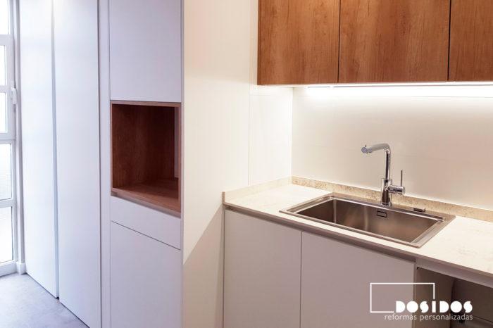 Reforma de una cocina con muebles blancos y madera, hueco decorativo en columna almacenaje, encimera dekton nilium.