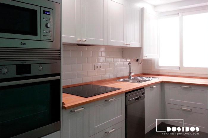 Reforma de una cocina con estilo vintage muebles en color blanco y encimera de madera.