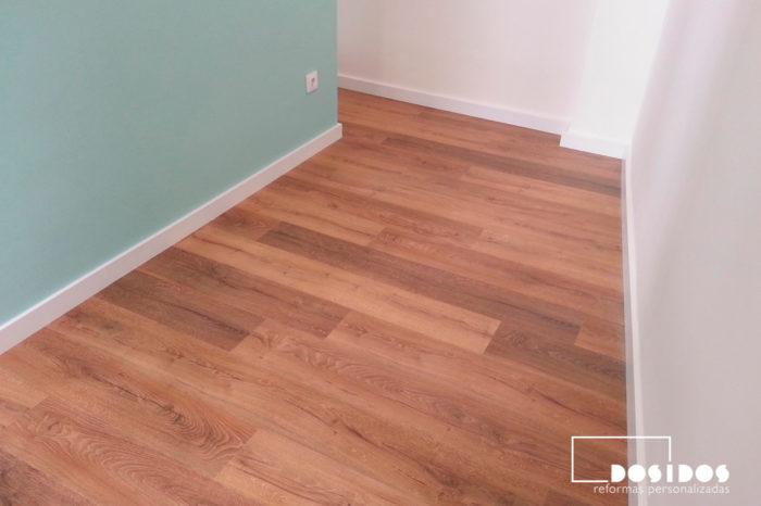 Vista del suelo con parquet y pared del vestidor en color verde.