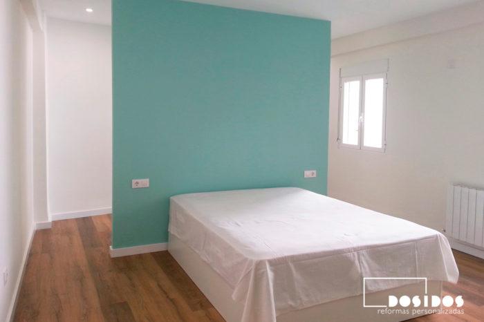 Habitación de matrimonio con vestidor abierto, tabique del cabezal pintada en color verde y suelo con parquet.